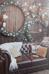 The room is decorated for the New Year. Christmas wreaths, white blanket and pillows on the couch.