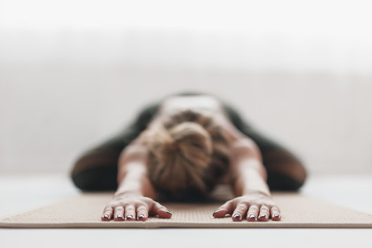 Anonymous stretching woman on mat