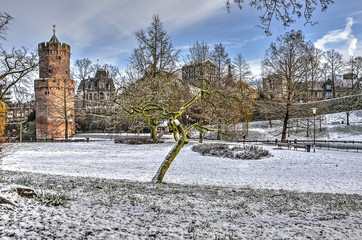 Kronenburg Park in downtwon Nijmegen, The Netherlands, with the medieval Gunpowder Tower covered with a thin layer of fresh snow on a cold day in winter
