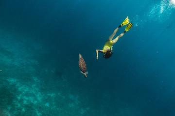 Caucasian cute girl underwater swimming with turtle