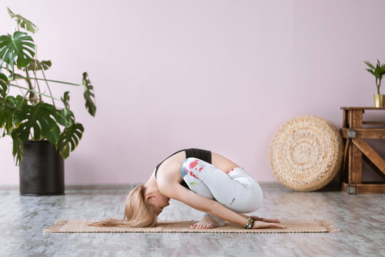 Yoga and fitness. Portrait of adult fit woman working out and practicing yoga at gym, Malasana pose