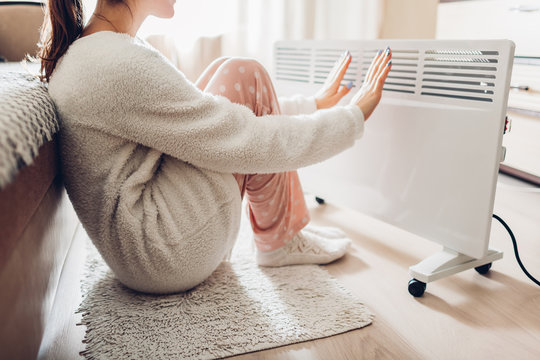 Using heater at home in winter. Woman warming her hands. Heating season.