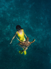 Caucasian cute girl underwater swimming with turtle