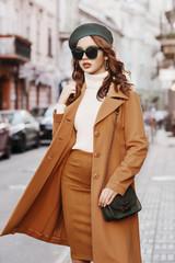 Outdoor portrait of young beautiful fashionable woman wearing trendy autumn coat, turtleneck,...