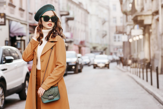 Outdoor portrait of young beautiful fashionable woman wearing trendy autumn coat, turtleneck, beret, sunglasses, with small shoulder bag, walking in street of european city. Copy, empty space for text