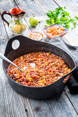 Traditional slow cooked Mexican chili con cane with mincemeat, beans and corn as top view in a modern design cast-iron roasting dish