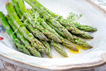 Traditional boiled green asparagus with butter sauce decorated with cress as closeup on a design plate