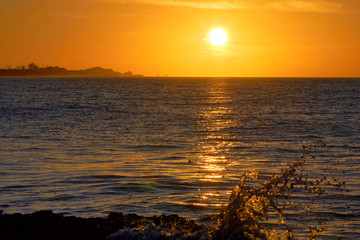 Seascape during sunset, dark water with golden sun path and evening sky