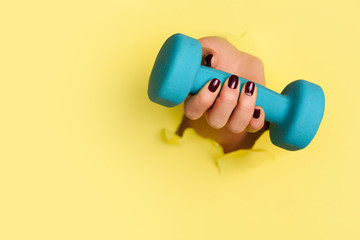 Woman hand holding blue dumbbell on yellow background. Fitness, sport, healthy lifestyle, diet concept. Banner with copy space