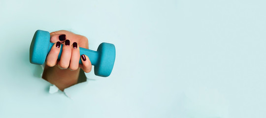 Woman hand holding blue dumbbell on blue background. Fitness, sport, healthy lifestyle, diet concept. Banner with copy space