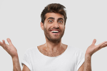 Isolated shot of cheerful gorgeous Caucasian man holds hands spread, rejoices good positive news or noticing someone, dressed in casual outfit, isolated over white background. People and emotions
