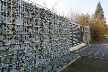 Automatic gate controlled by a remote control in the wall. Fence made of gabions.