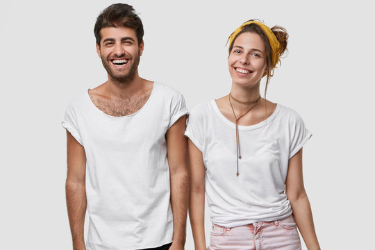 Human emotions, happiness and joy concept. Smiling woman and man wear casual white t shirt, smile broadly, rejoice good news, have positive look, isolated over studio wall indoor. Happy couple