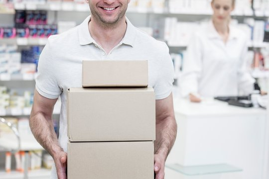 Courier carrying boxes in pharmacy