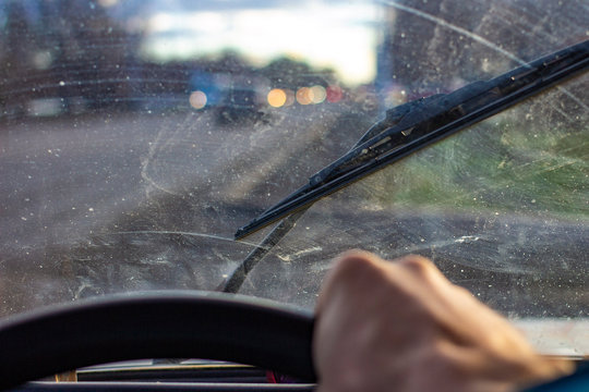 dirty scratched car windshield with wiper through blurred steering wheel with driver's hand on blurred background