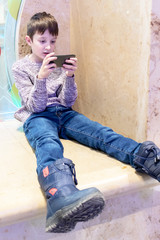 A boy sitting in the mall and hanging a smartphone