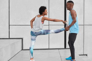 Black positive male instructor help female trainee to do exercises for flexibility, stand at stairs against white wall, have happy expressions, dressed in sportswear. People, sport and traning concept