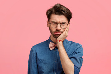 Portrait of sad stressful man keeps hand on cheek, looks desperately, feels toothache, has some trouble, dressed in fashionable stylish denim shirt and bowtie, isolated over pink background.