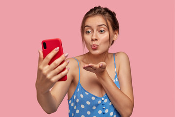 Pleasant looking girlfriend flirts with man over smart phone, makes air kiss during video call, holds mobile phone in front, wears casual summer dress, isolated over pink wall. Technology, leisure