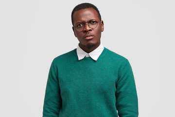 Angry dissatisfied black man frowns face has disappointed facial expression, vexed look, dressed in green jumper, discontnent with changing job position, isolated over white studio background