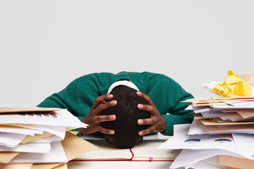 People, work, deadline and stress concept. Overworked dark skinned manager leans on table, keeps both hands on head, feels headache, works on new report, takes break, isolated on white wall.