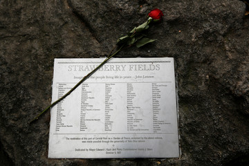 A flower rests on a plaque for former Beatle John Lennon in the Strawberry Fields section of New York's Central Park to mark the 38th anniversary of his death, in New York