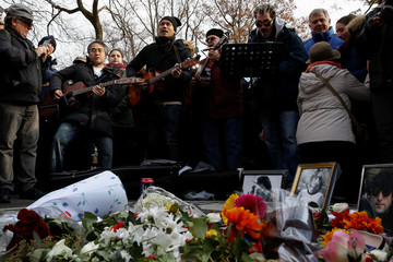 Musicians and people sing and play music in memory of former Beatle John Lennon at the Imagine mosaic in the Strawberry Fields section of New York's Central Park to mark the 38th anniversary of his death, in New York