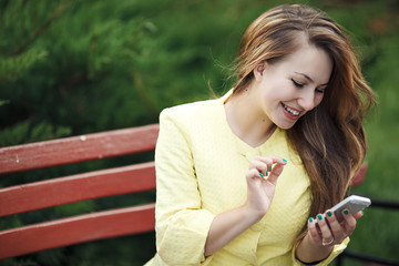 Beautiful stylish young woman sitting on a bench with a phone in her hands and smiling