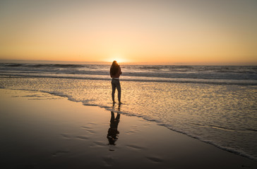 silhouette of woman on the beach at sunset.  Located in Redondo Beach California right outside Los Angeles.