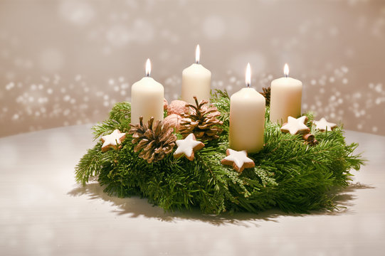 Fourth  Advent - decorated Advent wreath from fir and evergreen branches with white burning candles, tradition in the time before Christmas, warm background with festive bokeh and copy space