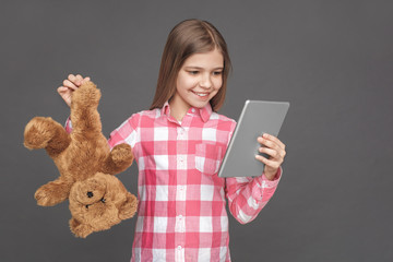 Freestyle. Girl standing isolated on grey with teddy bear indifferent looking at digital tablet excited