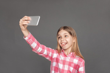Freestyle. Girl standing isolated on grey taking selfie on smartphone tongue out playful