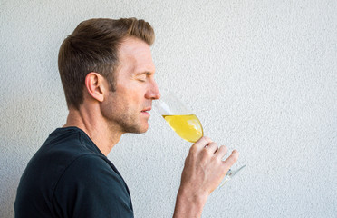 profile of a handsome Caucasian man with his eyes closed savoring a glass of champagne