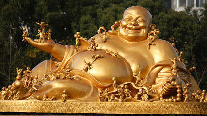 Golden buddha image with smaller figurines of children all over the body