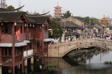 View from a bridge towards old traditional buildings, a buddhist temple pagoda and the channel in Qibao old town Shanghai, China