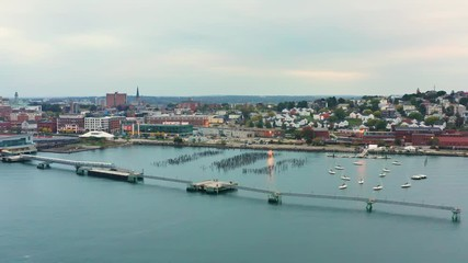 Fototapete - Aerial drone footage of the Portland, Maine waterfront, harbor, marina and skyline, at dusk (parallel panning)