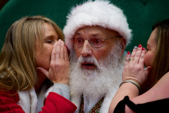 Santa Claus reacts as Tami McEleney and Patrice Conner whisper in his ear at the King of Prussia Mall, United States' largest retail shopping space, in King of Prussia