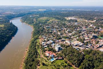 Town of Puerto Iguazu city centre aerial view. Tancredo Neves Bridge (Fraternity Bridge) border crossing Brazil—Argentina over the Iguassu River.