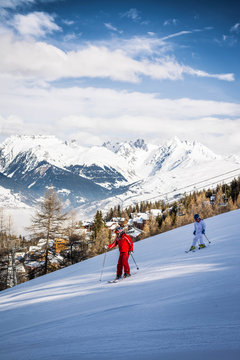 Two people skiing on a ski slope at La Plagne in the French Alps in Savoie, France