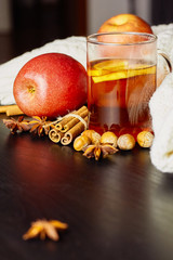 Glass cup of hot spicy drink with apple and orange slices, cinnamon and anise on dark wooden background