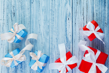Christmas gifts packed with ribbons on wooden background