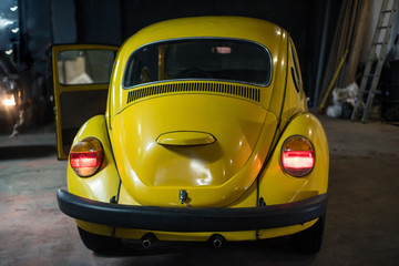 Close up of yellow classic car in workshop interior