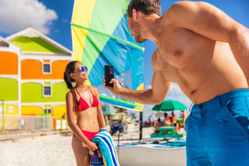 Wall Mural - Beach vacation couple taking phone pictures - man taking pictures of model woman posing in bikini sun bathing in summer. Florida travel.