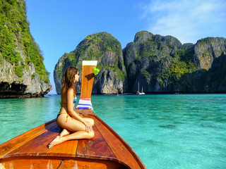 Young woman sitting at the front of longtail boat in Maya Bay on Phi Phi Leh Island, Krabi Province, Thailand