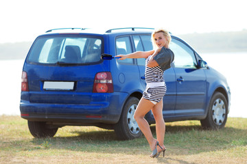 girl in a striped suit poses near blue car