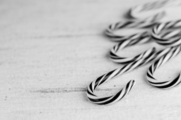 Black and white  stripes candy canes on a wooden background