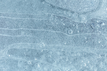 Frozen cracked ice surface background with air bubbles. Cold icy winter texture