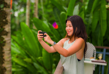young beautiful and happy Asian Chinese backpacker woman enjoying holidays at tropical rice terrace smiling delighted taking landscape photo with mobile phone