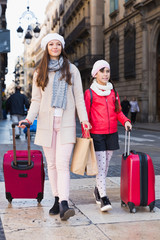 woman with daughter walking with bags