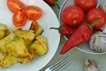 Fried potatoes on a white plate, tomatoes, red peppers and garlic. Top view.